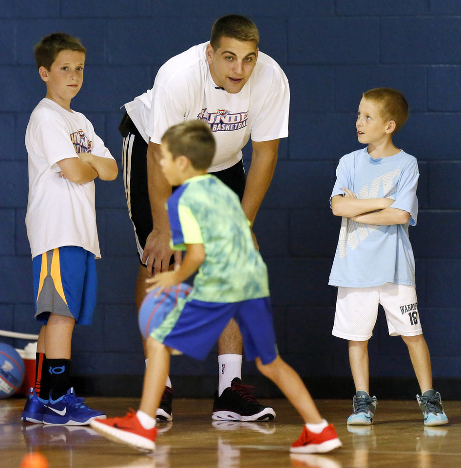 Photo - Thunder player Mitch McGary gives instructions to a camper during a visit to Thunder Youth Basketball Camp at Casady School in Oklahoma City, Wednesday, July 16, 2014. Photo by Nate Billings, The Oklahoman