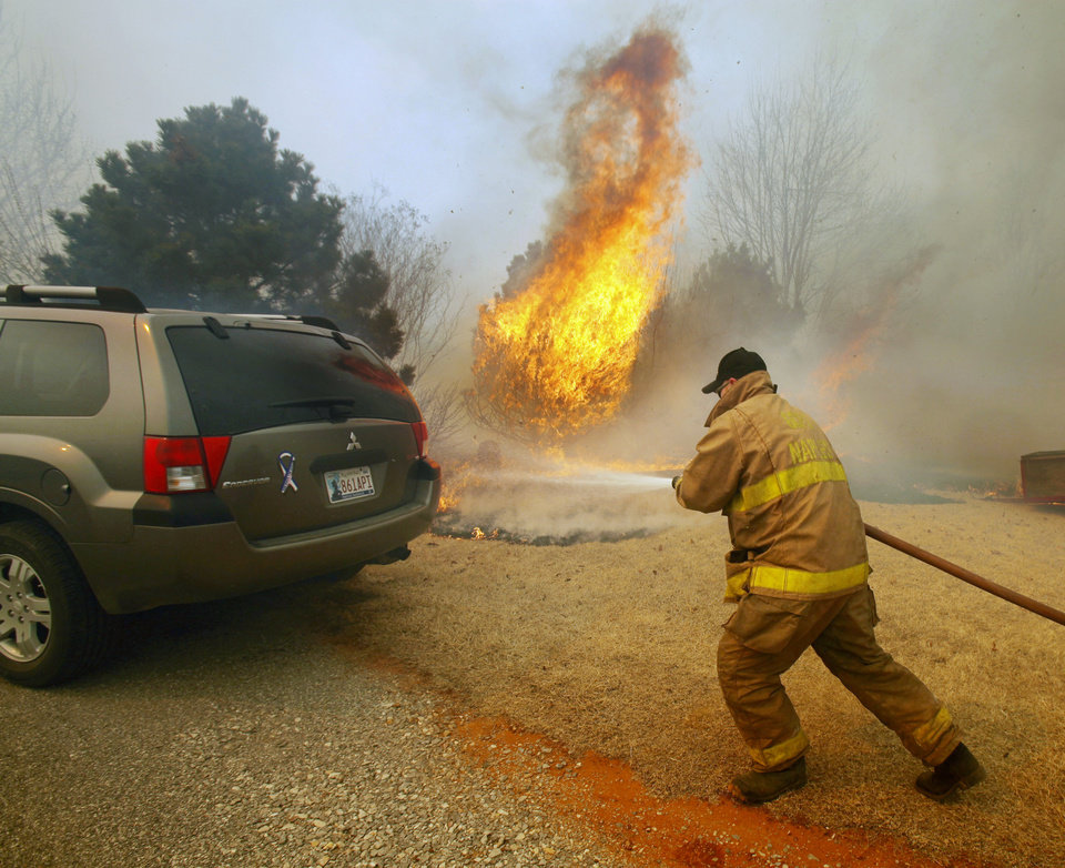 Photo - A fireman extinguishes a blaze just feet from an automobile on Western Ave as a large grass fire rages on Friday, March 11, 2011, in Goldsby, Okla. Photo by Steve Sisney, The Oklahoman