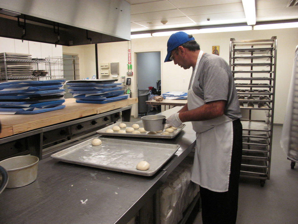 Photo - Volunteer Mike Sleem places unbaked rolls on a baking sheet bound for the oven at St. Elijah Antiochian Orthodox Christian Church. The rolls will be sold at the church's annual food festival and holiday bake sale Friday and Saturday at 15000 N May. Photo by Carla Hinton, The Oklahoman