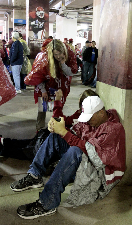 Fans wait under the stands as rain and the threat of lightning delay a college football game between the University of Oklahoma Sooners (OU) and the Texas Tech Red Raiders at Gaylord Family-Oklahoma Memorial Stadium in Norman, Okla., on Saturday, Oct. 26, 2013. Photo by Steve Sisney, The Oklahoman