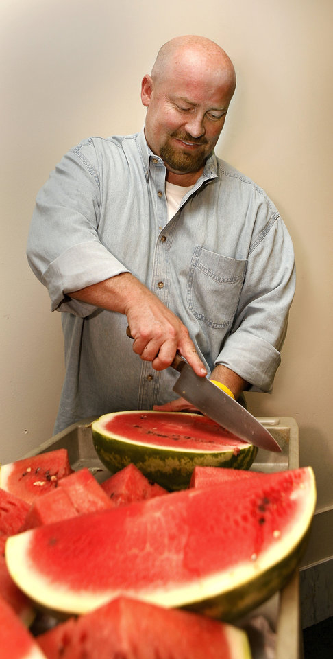 Photo - State Rep. Joe Dorman, D-Rush Springs, treats workers and officials Thursday at the state Capitol to sliced watermelon from Rush Springs to promote the city's annual melon festival later this month. Photo by Jim Beckel, The Oklahoman   Jim Beckel