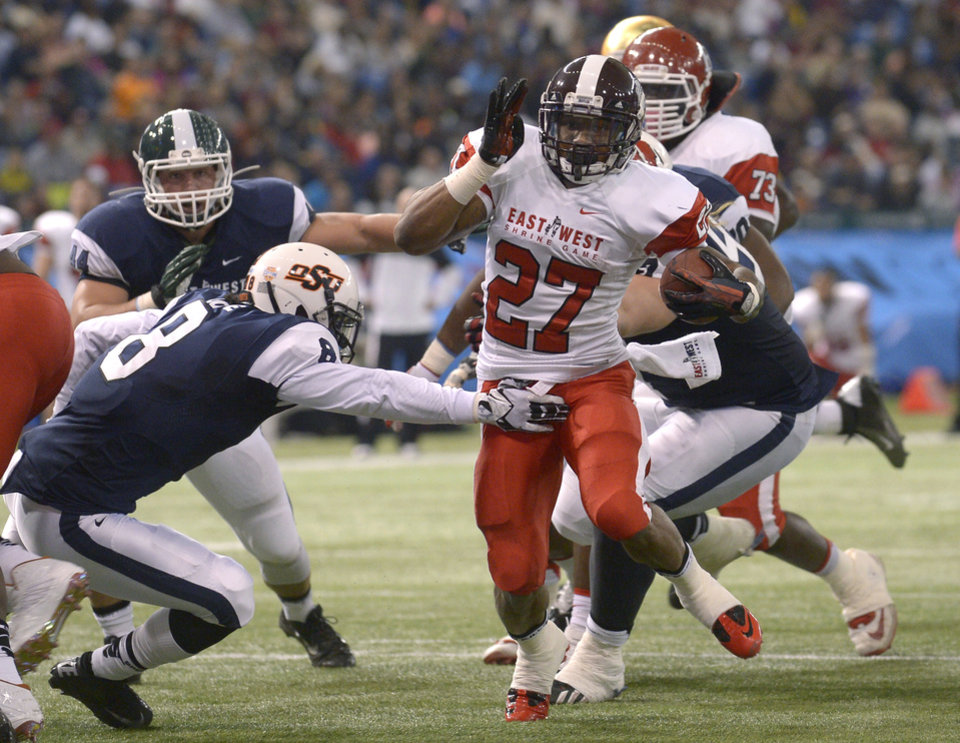 Photo - East running back LaDarius Perkins (27), of Mississippi State, rushes for yardage past West safety Daytawion Lowe (8), of Oklahoma State, during the first half of the East-West Shrine Classic NCAA college football game in St. Petersburg, Fla., Saturday, Jan. 18, 2014. (AP Photo/Phelan M. Ebenhack)
