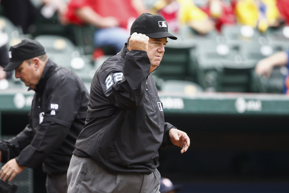Photo - Umpire Joe West (22) signals an out after a challenged call at first base on a grounder by Texas Rangers' Shin-Soo Choo to Houston Astros second baseman Jose Altuve during the first inning of a baseball game, Sunday, April 13, 2014, in Arlington, Texas. The original call that Choo was safe was challenged. (AP Photo/Jim Cowsert)