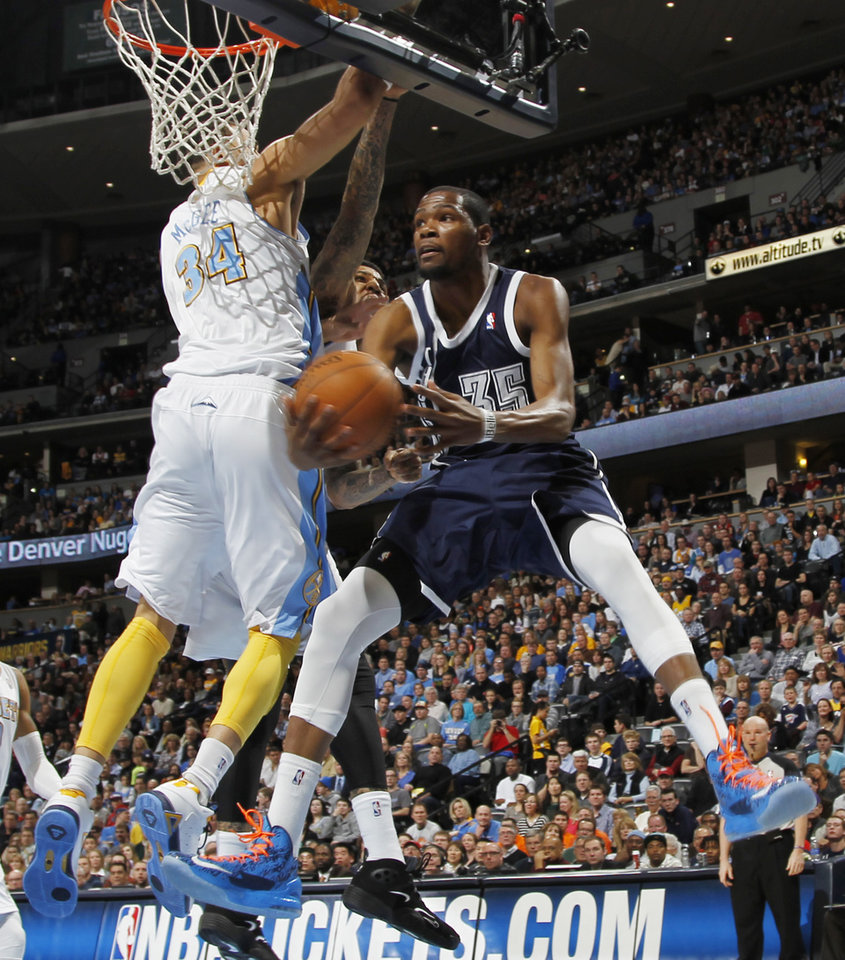 Oklahoma City Thunder forward Kevin Durant, right, goes up for a reverse layup past Denver Nuggets forward JaVale MGee in the first quarter of an NBA basketball game in Denver on Friday, March 1, 2013. (AP Photo/David Zalubowski) ORG XMIT: CODZ110