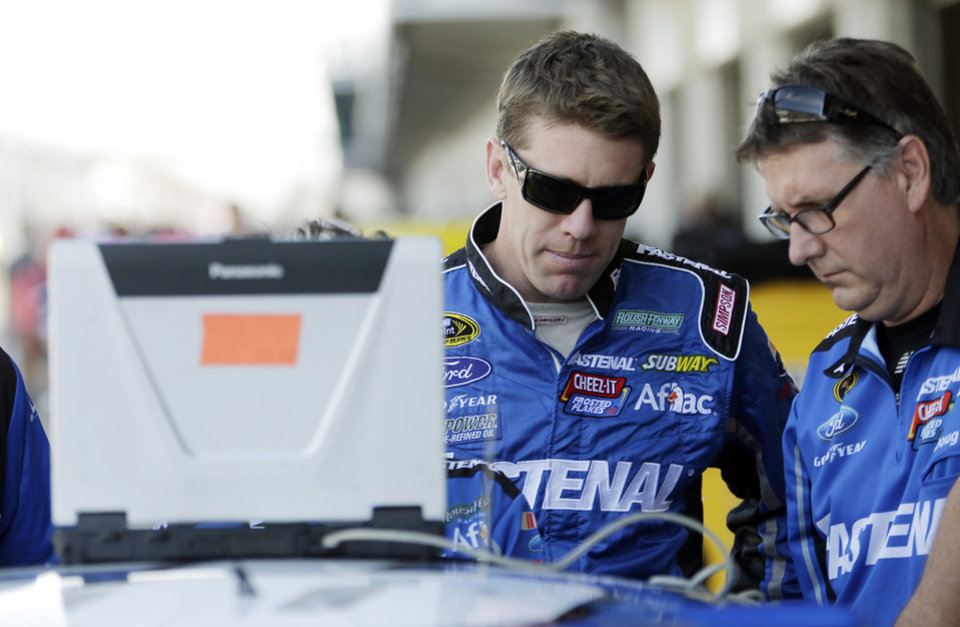 Photo - Driver Carl Edwards, left,  talks with a crew member before practice for the Brickyard 400 Sprint Cup series auto race at the Indianapolis Motor Speedway in Indianapolis, Friday, July 25, 2014. (AP Photo/AJ Mast)