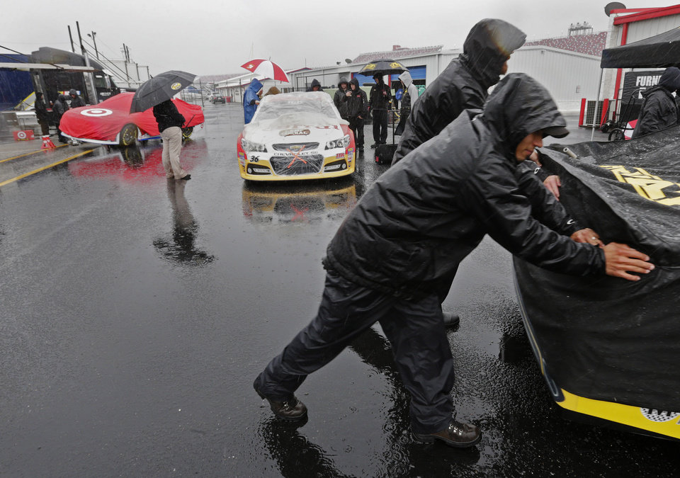Photo - Pit crew members push their cars through the rain to the inspection garage at the Talladega Superspeedway in Talladega, Ala., Saturday, May 4, 2013. Rain threatens Saturday's qualifying for the Aaron's 499 race at Talladega. (AP Photo/Dave Martin)