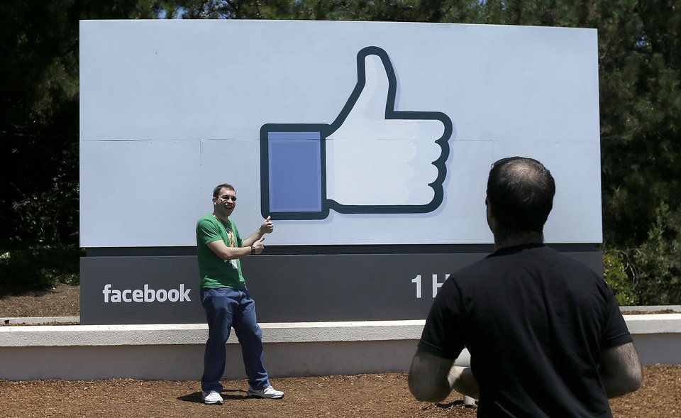 Photo - In this June 11, 2014 photo, a man poses for photographs in front of the Facebook sign on the Facebook campus in Menlo Park, Calif. In the coming weeks, Facebook will start offering advertisers another way to tailor ads in the U.S., based on information gathered from other websites you visit and the apps you use. (AP Photo/Jeff Chiu)