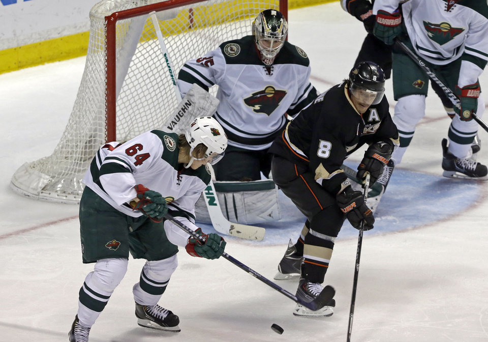 Photo - Anaheim Ducks right winger Teemu Selanne (8), of Finland, maneuvers the puck with Minnesota Wild center Mikael Granlund (64), of Finland, and goalie Darcy Kuemper (35) defending in the second period of an NHL hockey game in Anaheim, Calif., Tuesday, Jan. 28, 2014. (AP Photo/Reed Saxon)