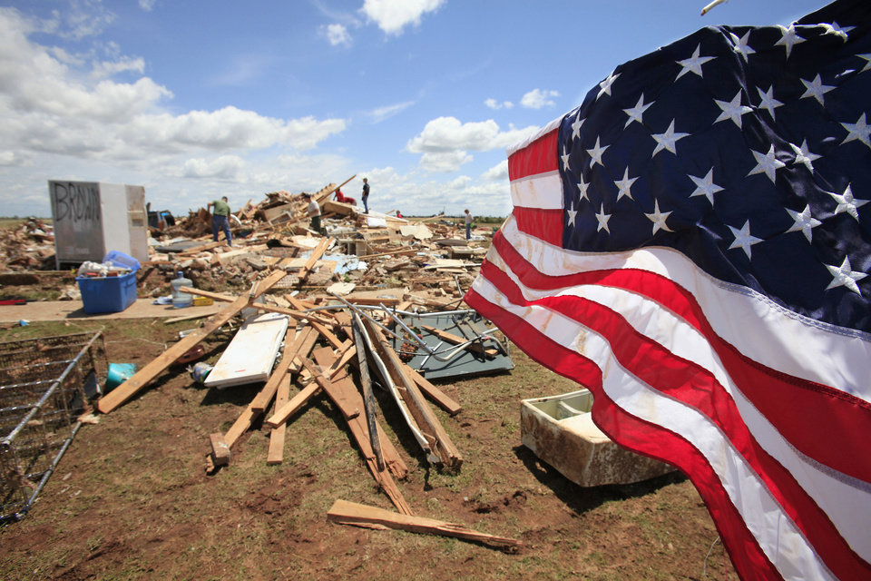 Photo - Tornado aftermath cleanup  May 25, 2011.  An American flag hangs from a small tree in the yard of Chad Brown and Becky Brown's house the was hit by the May 24, 2011 tornado.   David McDaniel - The Oklahoman, Archive