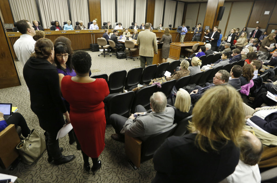 Speakers line up to speak in opposition of a bill that would remove funding for abortions during a meeting of the Senate Health Education and Welfare committee at the Capitol Thursday, Jan. 17, 2013 in Richmond, Va. The committee killed the bill.  (AP Photo/Steve Helber)