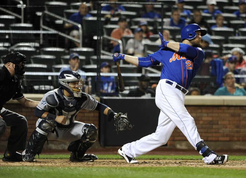 Photo - New York Mets' Lucas Duda, right, hits an RBI double off of San Diego Padres starting pitcher Andrew Cashner to tie the score 2-2 in the fourth inning as Rene Rivera catches for the Padres in a baseball game at Citi Field on Friday, June 13, 2014, in New York. (AP Photo/Kathy Kmonicek)