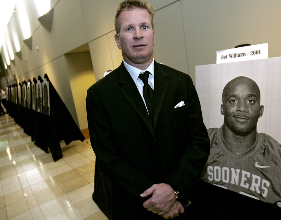 Photo - University of Arizona head coach Mike Stoops poses near a photo of previous award winner Roy Williams prior to the Jim Thorpe Award Banquet at the National Cowboy and Western Heritage Museum on Tuesday, Feb. 12, 2008. By John Clanton, The Oklahoman ORG XMIT: KOD
