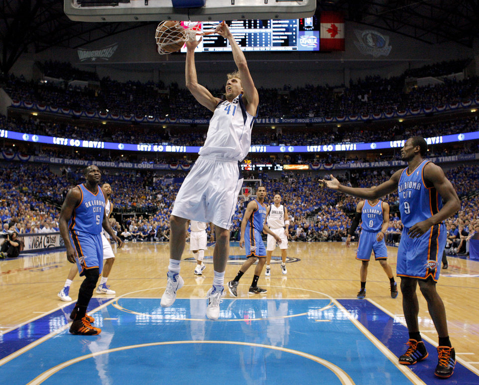 Dirk Nowitzki (41) of Dallas dunks the ball between Oklahoma City\'s Kendrick Perkins (5) and Serge Ibaka (9)during game 5 of the Western Conference Finals in the NBA basketball playoffs between the Dallas Mavericks and the Oklahoma City Thunder at American Airlines Center in Dallas, Wednesday, May 25, 2011. Photo by Bryan Terry, The Oklahoman