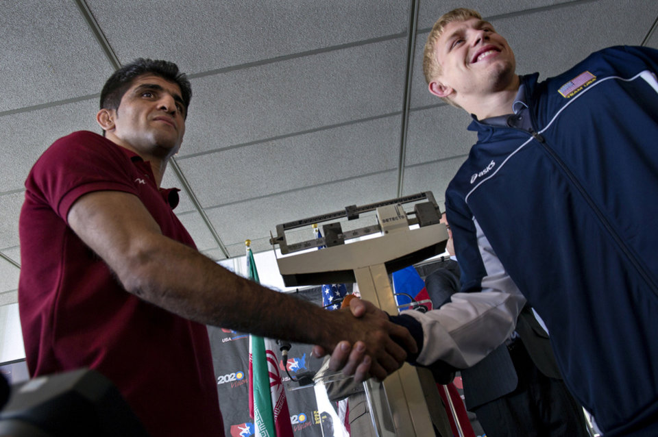 Photo - Wrestlers in the 74 kilogram weight class Hassan Tahmasebi, left, of Iran, shakes hands with USA wrestler Kyle Dake, of Ithaca, N.Y., during a news conference at U.N. headquarters, Tuesday, May 14, 2013, announcing the