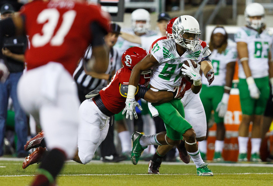 Photo - Oregon wide receiver Darren Carrington (87) runs downfield with a South Dakota defender's arms wrapped around him during the second quarter of an NCAA college football game in Eugene, Ore., Saturday, Aug. 30, 2014. (AP Photo/Ryan Kang)