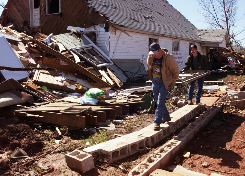 Tornado damage: Johnny Green, Orlando, Oklahoma, helps Rodney Wiss, Mulhall, carry tables out of the damaged church in Mulhall.  The church at left was blown off the foundation at right.