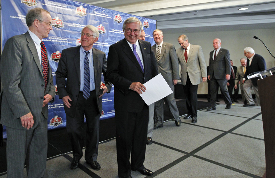 Photo -   Virginia Tech President Charles Steger, third from left, smiles as he and others arrive for a media availability after a BCS presidential oversight committee meeting, Tuesday, June 26, 2012, in Washington. A committee of university presidents on Tuesday approved the BCS commissioners' plan for a four-team playoff to start in the 2014 season. (AP Photo/Alex Brandon)