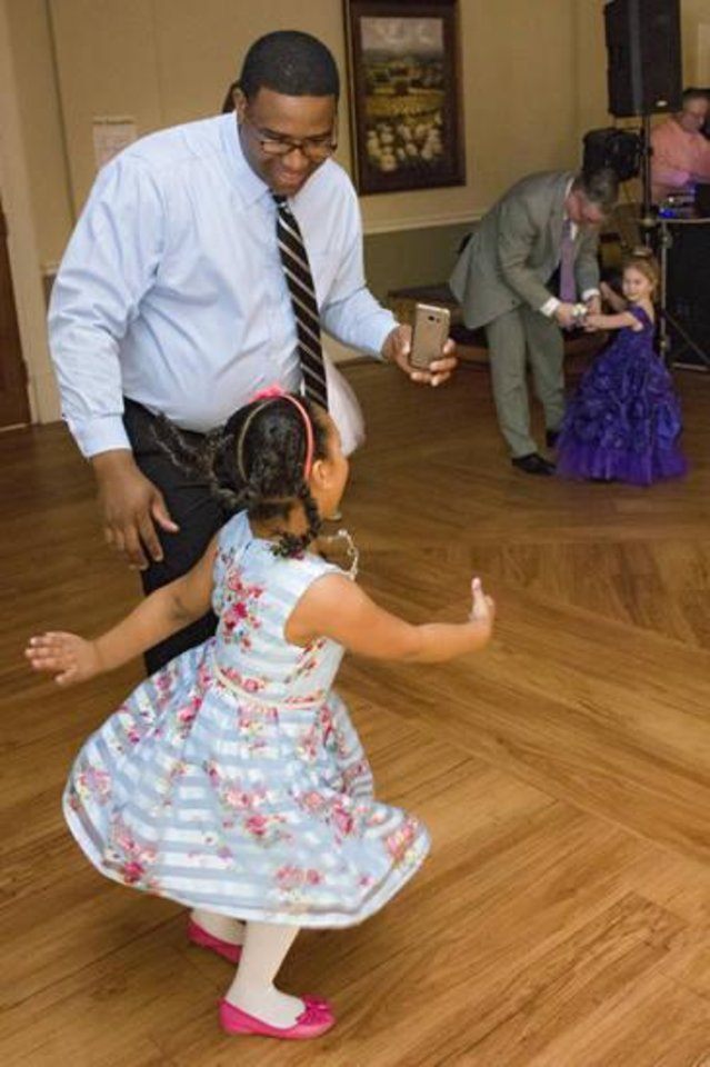 Photo -  Aubrey Mason, 5, and her father, Daniel Mason, dance at the Edmond Parks and Recreation Daddy-Daughter Dance. [PHOTO BY ERIECH TAPIA, FOR THE OKLAHOMAN]