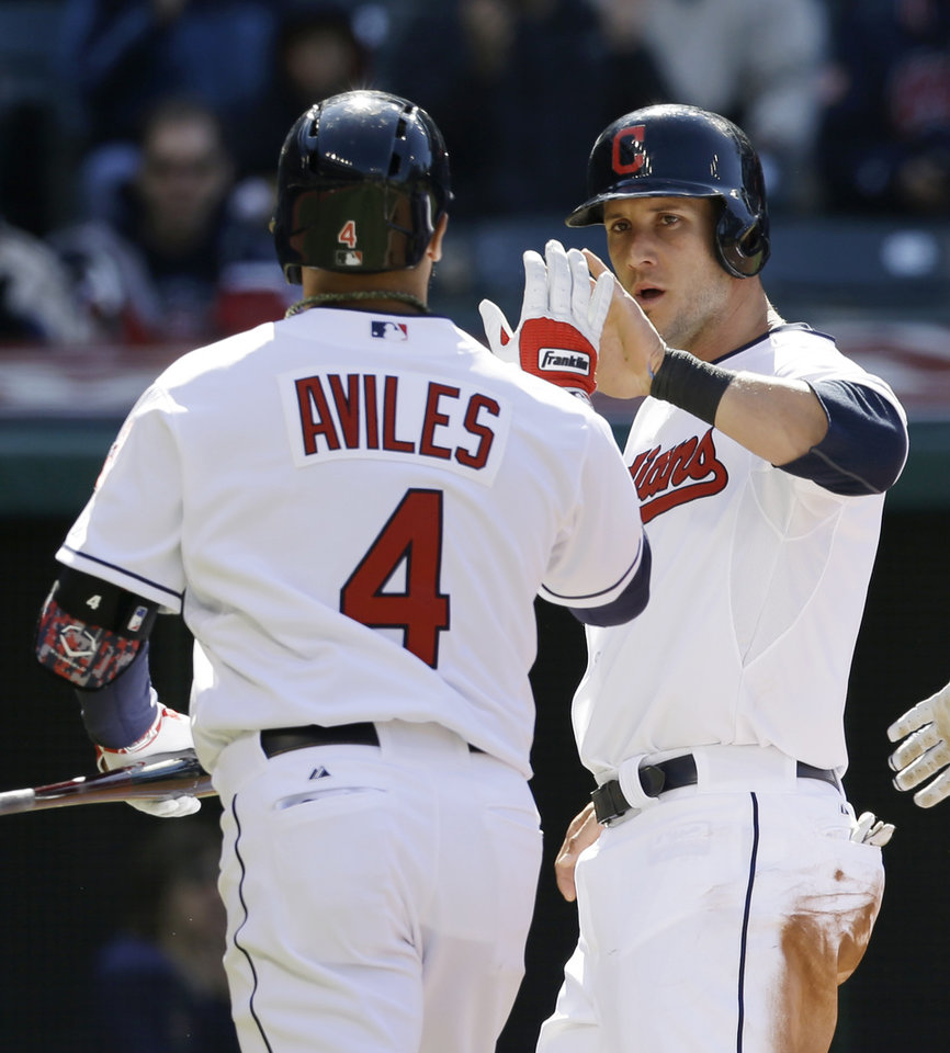 Photo - Cleveland Indians' Yan Gomes, right, congratulates Mike Aviles after Aviles hit a sacrifice fly off San Diego Padres starting pitcher Robbie Erlin in the third inning in the second game of the MLB baseball doubleheader, Wednesday, April 9, 2014, in Cleveland. Gomes scored on the play. (AP Photo/Tony Dejak)