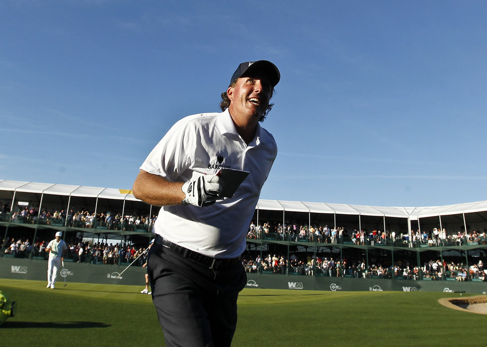 Photo - Phil Mickelson smiles to the cheering crowd as he walks off the 16th green during the second round of the Phoenix Open golf tournament Friday, Feb. 1, 2013, in Scottsdale, Ariz. (AP Photo/Ross D. Franklin)