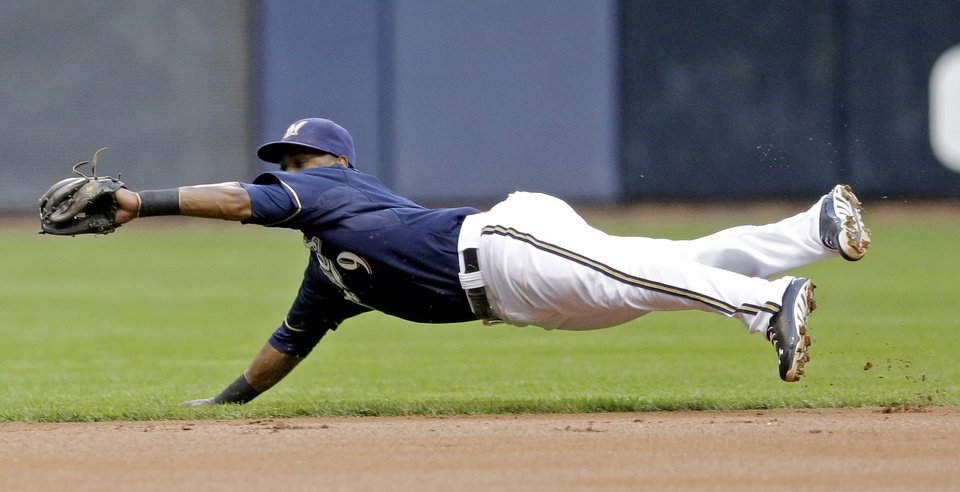 Photo - Milwaukee Brewers shortstop Jean Segura makes a diving catch on a ball hit by Texas Rangers' Ian Kinsler during the first inning of a baseball game Wednesday, May 8, 2013, in Milwaukee. (AP Photo/Morry Gash)
