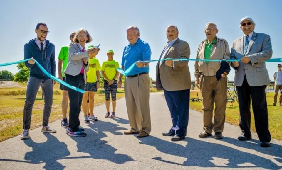 Photo - Civic leader cut the ribbon during The Oklahoma City Community Foundation's 50th anniversary ceremony with a Oklahoma River Trail dedication along the north shore in Oklahoma City, Okla. on Tuesday, May 14, 2019. Civic leaders, runners, cyclists and walkers gathered to dedicate the Oklahoma City Community Foundation River Trail that was highlighted with 800 trees, stone park benches and wildflower growing areas. [Chris Landsberger/The Oklahoman]