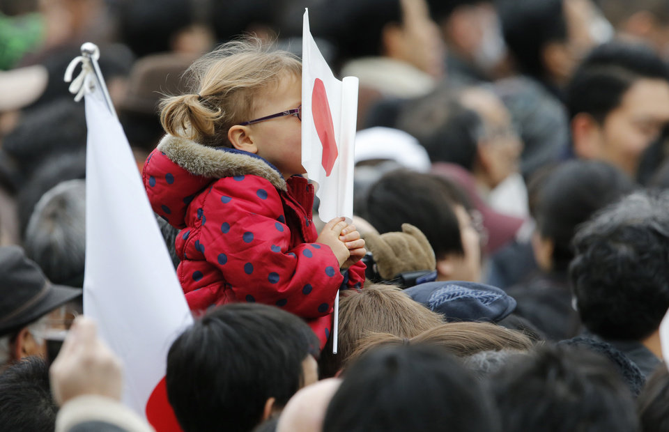 A girl covers her face with a Japanese national flag at the Imperial Palace as Emperor Akihito and his imperial family members receive greetings from well-wishers to celebrate his 79th birthday, Sunday, Dec. 23, 2012, in Tokyo. (AP Photo/Shizuo Kambayashi)