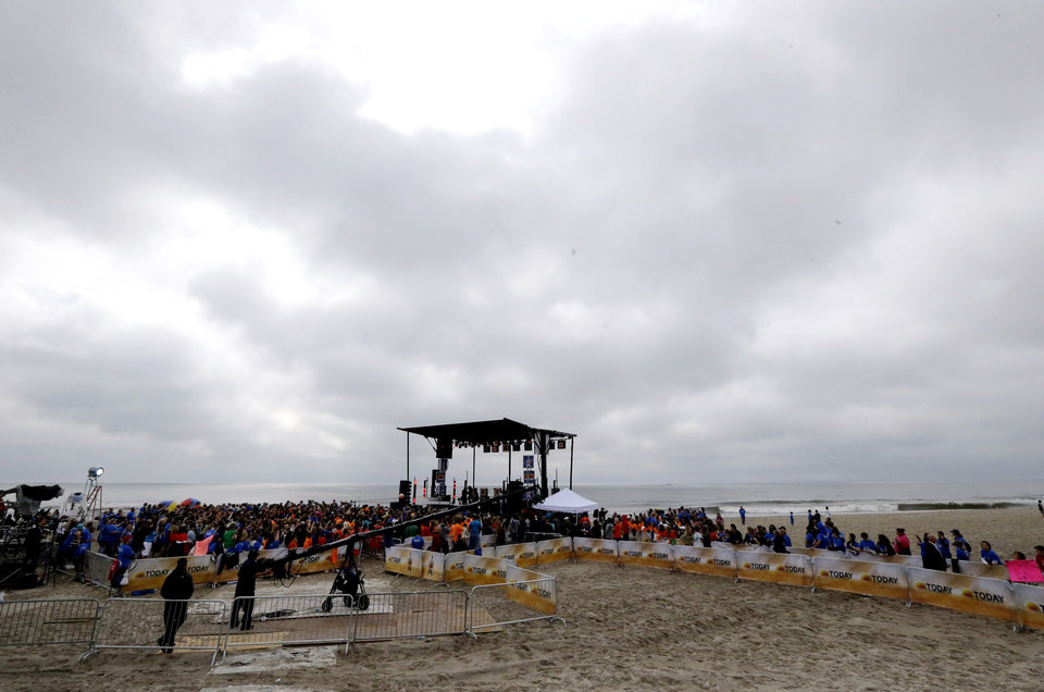 Photo - People gather around a stage as musical group Fun performs on the beach, Friday, May 24, 2013, in Seaside Heights, N.J. New Jersey Gov. Chris Christie cut a ribbon to symbolically reopen the state's shore for the summer season, seven months after being devastated by Superstorm Sandy. Several beach communities have annual beach ribbon cuttings, announcing they are back in business. But this year's ceremonies are more poignant seven months after a storm that did an estimated $37 billion of damage in the state. (AP Photo/Julio Cortez)