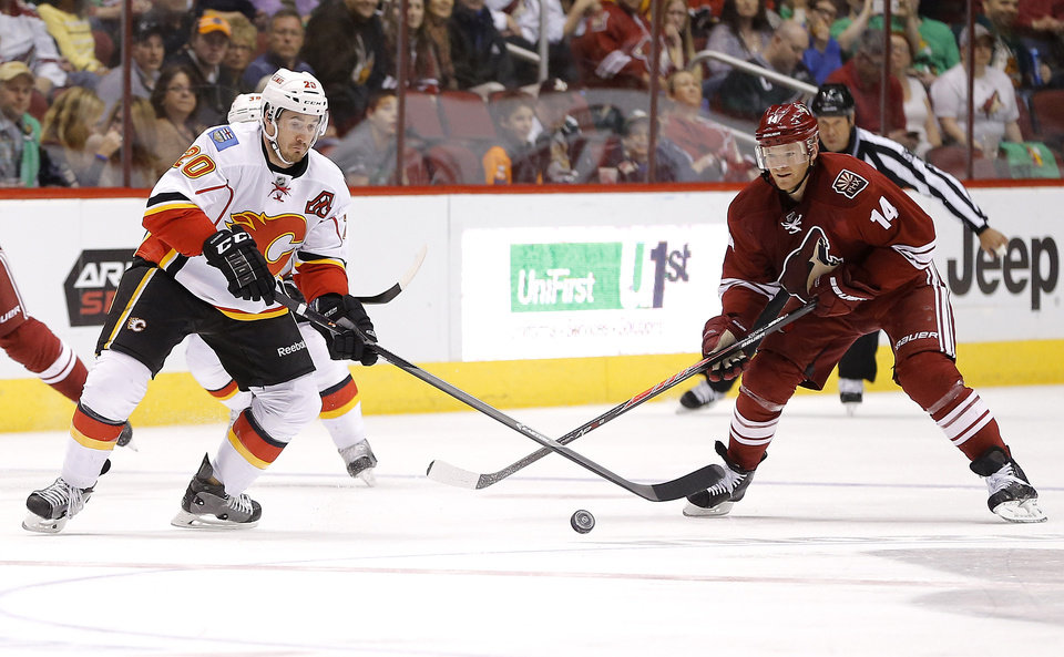Photo - Calgary Flames' Curtis Glencross, left, and Phoenix Coyotes' Jeff Halpern chase down the puck during the first period of an NHL hockey game on Saturday, March 15, 2014, in Glendale, Ariz. (AP Photo/Matt York)