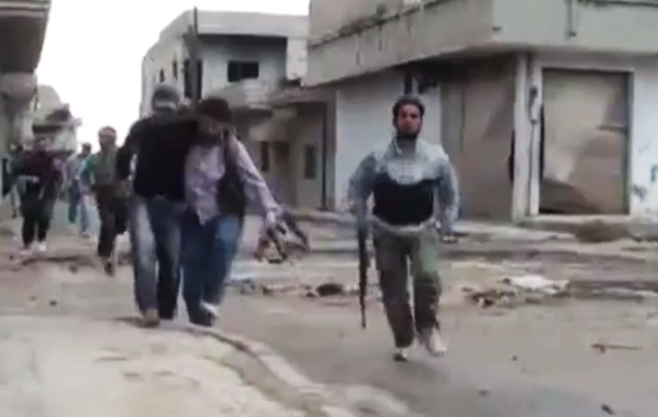 Photo -   In this image made from amateur video released by the Shaam News Network and accessed Monday, May 14, 2012, purports to show a Syrian rebel helping an injured man in Rastan, Homs, Syria. Syrian troops shelled the rebel-held town, sparking intense clashes that sent bloodied victims flooding into hospitals and clinics, activists said. The violence around the country is eroding an internationally brokered peace plan that many observers see as the last hope to calm the 14-month-old crisis. (AP Photo/Shaam News Network via AP video) TV OUT, THE ASSOCIATED PRESS CANNOT INDEPENDENTLY VERIFY THE CONTENT, DATE, LOCATION OR AUTHENTICITY OF THIS MATERIAL