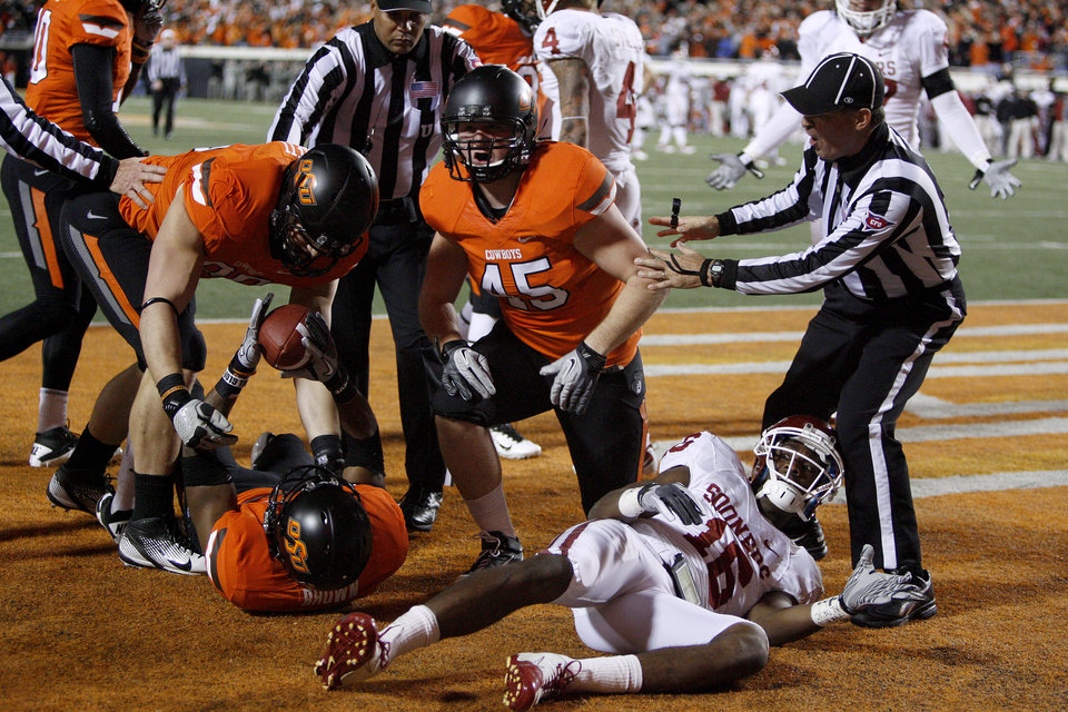 Photo - Oklahoma State's Brodrick Brown (19) comes up with an interception next to Oklahoma's Jaz Reynolds (16) during the Bedlam college football game between the Oklahoma State University Cowboys (OSU) and the University of Oklahoma Sooners (OU) at Boone Pickens Stadium in Stillwater, Okla., Saturday, Dec. 3, 2011. Photo by Bryan Terry, The Oklahoman