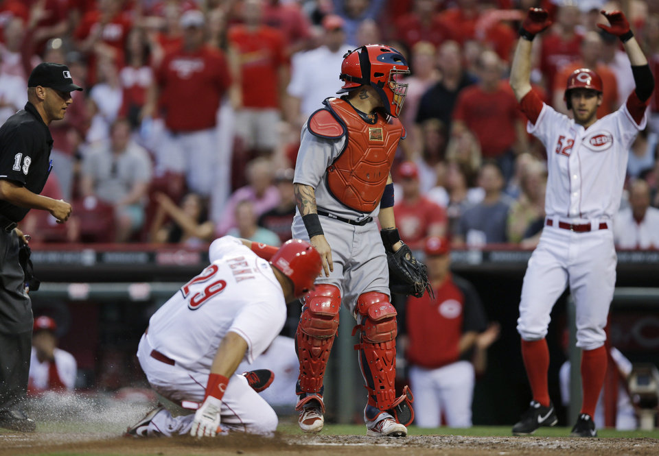 Photo - Cincinnati Reds' Brayan Pena (29) scores on a hit by Zack Cozart in the fifth inning of a baseball game while St. Louis Cardinals catcher Yadier Molina waits for the throw, Saturday, May 24, 2014, in Cincinnati. Tony Cingrani celebrates at right. (AP Photo/Al Behrman)