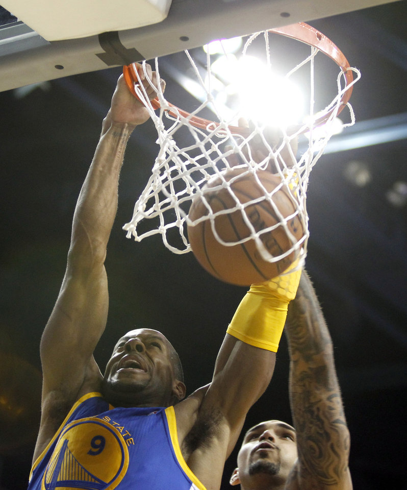 Photo - Golden State Warriors guard Andre Iguodala, left, dunks the ball with Los Angeles Lakers center Robert Sacre, right, defending in the second quarter during an NBA basketball preseason game Saturday, Oct. 5, 2013, in Ontario, Calif.  (AP Photo/Alex Gallardo)