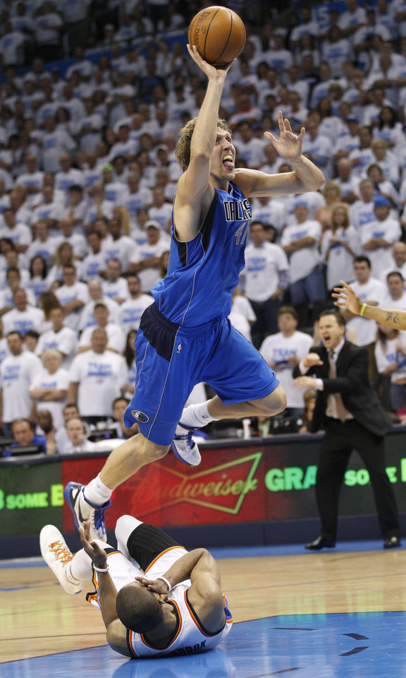 Photo -   Dallas Mavericks forward Dirk Nowitzki, top, fouls Oklahoma City Thunder guard Russell Westbrook, bottom, as he shoots in the fourth quarter of Game 2 in the first round of the NBA basketball playoffs, in Oklahoma City, Monday, April 30, 2012. Oklahoma City won 102-99. (AP Photo/Sue Ogrocki)