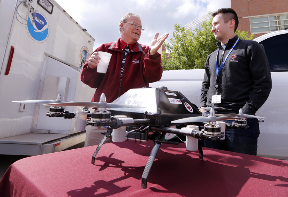 Photo -  Ken Carson, the director of the University of Oklahoma's Department of Aviation, shows off a drone with Hunter Luna earlier this year.  [Photo by Steve Sisney, The Oklahoman]