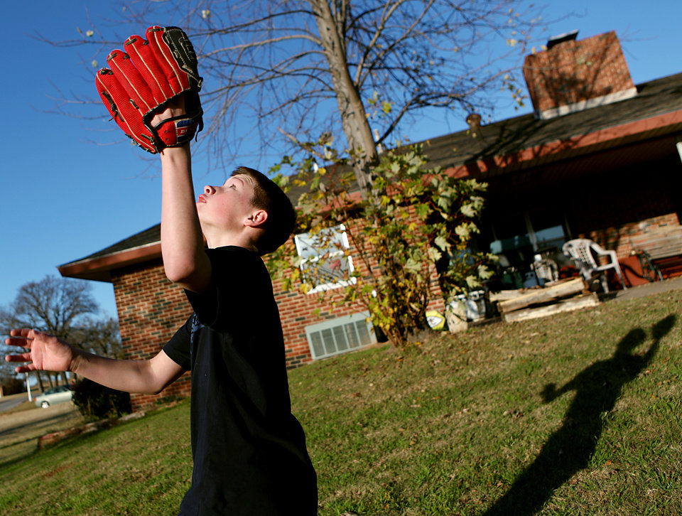 Photo - Chris, a resident at Boys Ranch Town in Edmond, plays in the yard outside one of the houses on Monday, Nov. 30, 2009. By John Clanton, The Oklahoman ORG XMIT: KOD