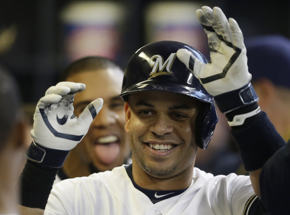 Photo - Milwaukee Brewers' Aramis Ramirez reacts in the dugout after his home run against the New York Yankees in the third inning of a baseball game on Saturday, May 10, 2014, in Milwaukee. Brewers' Carlos Gomez, background, also reacts. (AP Photo/Jeffrey Phelps)