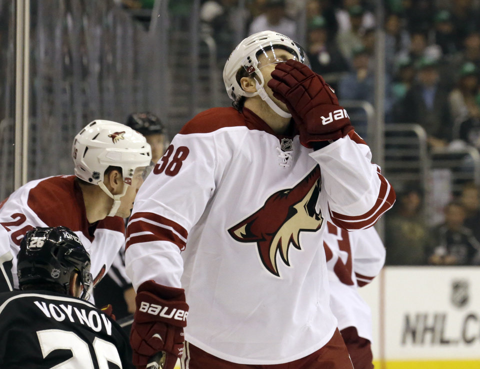 Photo - Phoenix Coyotes center Brandon McMillan (38) comes away with a bloody nose after a collision with the Los Angeles Kings in the first period of an NHL hockey game in Los Angeles Monday, March 17, 2014.  (AP Photo/Reed Saxon)