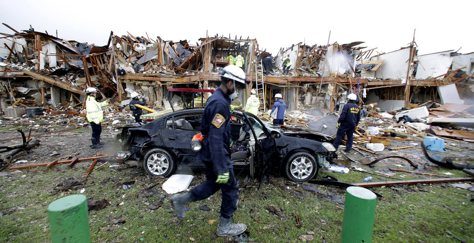 Photo - FILE - In this April 18, 2013, file photo, firefighters conduct search and rescue of an apartment destroyed by an explosion at the the West Fertilizer Co. in West, Texas. The Texas company that operated the fertilizer plant where a thunderous explosion in April killed 15 people is facing $118,300 in fines for two dozen serious safety violations, including a failure to have an emergency response plan, federal officials said Thursday, Oct. 10, 2013.  (AP Photo/LM Otero, File)