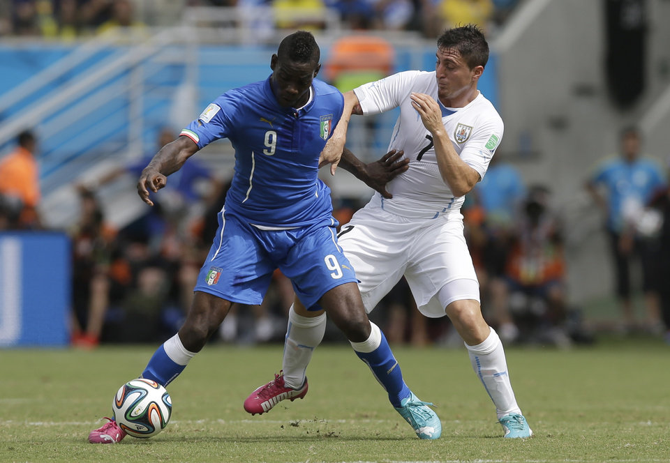 Photo - Italy's Mario Balotelli, left, and Uruguay's Cristian Rodriguez challenge for the ball during the group D World Cup soccer match between Italy and Uruguay at the Arena das Dunas in Natal, Brazil, Tuesday, June 24, 2014. (AP Photo/Andrew Medichini)