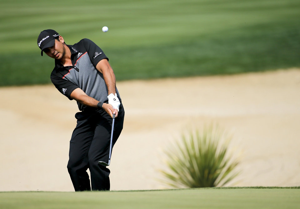 Photo - Jason Day hits a chip shot on the 17th hole in his match against Louis Oosthuizen, of South Africa, during the fourth round of the Match Play Championship golf tournament. Saturday, Feb. 22, 2014, in Marana, Ariz. (AP Photo/Matt York)