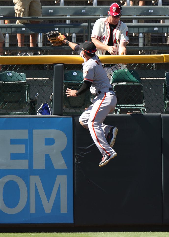 Photo - San Francisco Giants left fielder Gregor Blanco climbs the fence in a failed attempt to catch a three-run home run by Colorado Rockies' Nolan Arenado in the fifth inning of the Rockies' 9-2 victory in a baseball game in Denver on Wednesday, Sept. 3, 2014. (AP Photo/David Zalubowski)