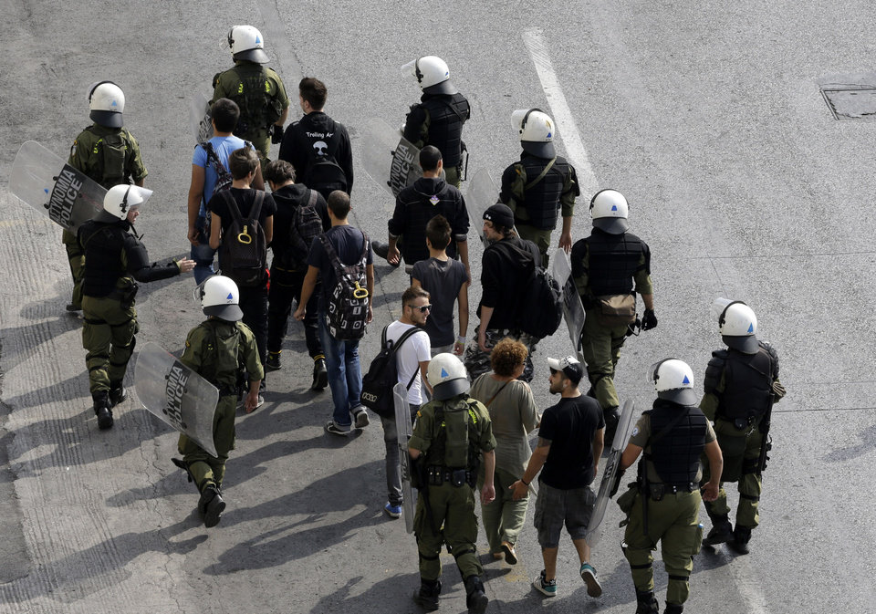 Civilians are detained as a precaution by riot police, prior to an protest in Athens on Tuesday Oct. 9, 2012. German Chancellor Angela Merkel makes her first visit to Greece since the eurozone crisis began here three years ago. Her five-hour stop is seen by the government as a historic boost for the country's future in Europe's shared currency, but by protesters as a harbinger of more austerity and hardship. More than 7,000 police will be on hand, cordoning off parks and other sections of central Athens, to keep demonstrators away from the German leader who is due to arrive Tuesday in the Greek capital for talks with conservative Prime Minister Antonis Samaras. (AP Photo/Dimitri Messinis)
