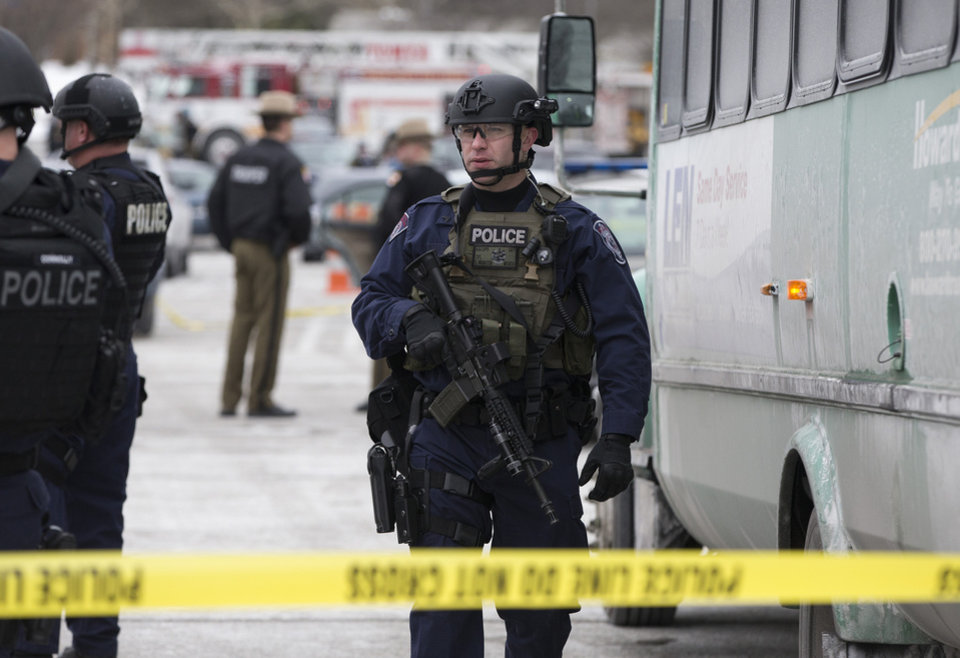 Photo - A heavily armed police officer walks on scene after a shooting at The Mall in Columbia on Saturday, Jan. 25, 2014 in Columbia, Md. Police say three people died in a shooting at the mall in suburban Baltimore, including the presumed gunman. (AP Photo/ Evan Vucci)