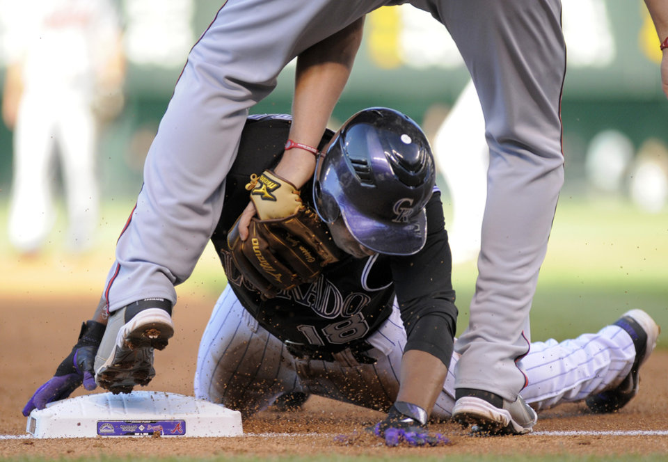 Photo -   Colorado Rockies' Jonathan Herrera beats the tag by Atlanta Braves' Chipper Jones to steal third during the first inning of a baseball game, Friday, May 4, 2012, in Denver. (AP Photo/Jack Dempsey)
