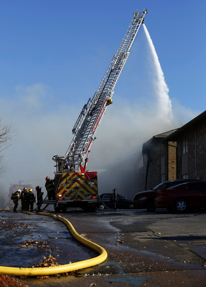 Firefighters use a ladder truck to put water on a blaze Wednesday at the Eden Cove Apartments in Midwest City. Photo by Garett Fisbeck, For The Oklahoman <strong>Garett Fisbeck</strong>