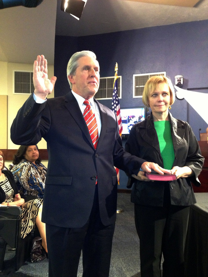 Edmond Ward 4 Councilman Nick Massey takes the oath of office. His wife, Dr. Karen Mahlmeister, holds the Bible. PHOTO BY DIANA BALDWIN, THE OKLAHOMAN. <strong>Diana Baldwin - THE OKLAHOMAN</strong>