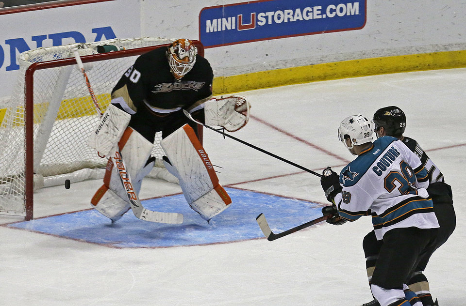 Photo - Anaheim Ducks goalie goalie Viktor Fasth (30), of Sweden, blocks a shot on goal (after review ruled no goal) as defenseman Francois Beauchemin (23) and San Jose Sharks center Logan Couture (39) watch in the third period of an NHL hockey game in Anaheim, Calif., Monday, March 25, 2013. The Sharks won, 5-3. (AP Photo/Reed Saxon)