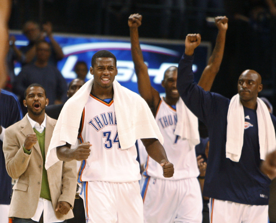 Photo - FIRST REGULAR SEASON WIN / CELEBRATE / CELEBRATION: Oklahoma City Thunder guard Desmond Mason (34) cheers from the bench late in the fourth quarter of an NBA basketball game against the Minnesota Timberwolves in Oklahoma City, Sunday, Nov. 2, 2008. Oklahoma City won the game 88-85. From left are John Lucas III, Mason, Joe Smith and Damien Wilkins. (AP Photo/Sue Ogrocki) ORG XMIT: OKSO105