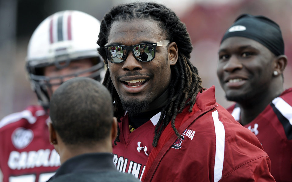 South Carolina defensive end Jadeveon Clowney talks with teammates on the sidelines during the second half of an NCAA college football game against Wofford, Saturday, Nov. 17, 2012, in Columbia, S.C. Clowney did not dress out for the game after being injured. South Carolina defeated Wofford 24-7. (AP Photo/Stephen Morton)